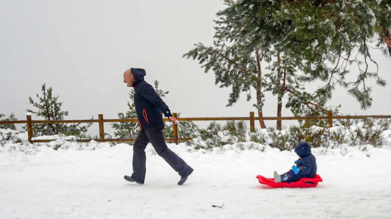 Un padre tira del trineo de su hijo durante el temporal de nieve en la Sierra de Madrid, en el Puerto de Navacerrada