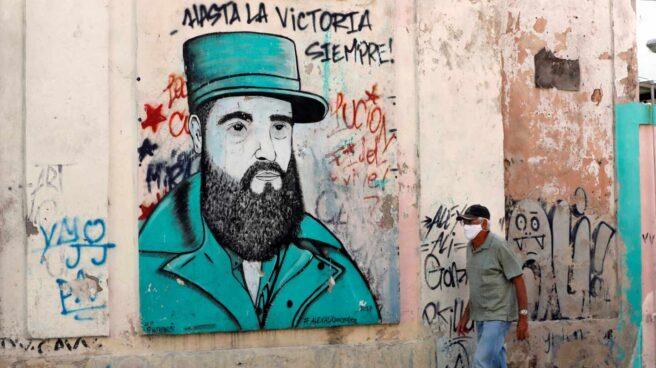 Un cubano pasa cerca de un dibujo de Fidel Castro con uno de sus lemas
