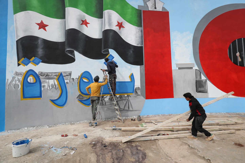 Unos jóvenes pintan un muro con la palabra 'Revolución' en árabe en Idlib, Siria