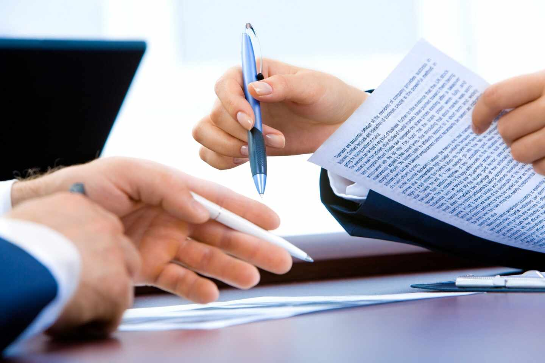 Dos personas firman unos papeles