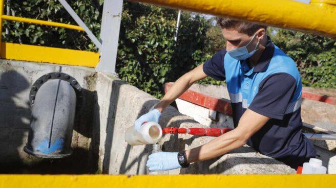 Un técnico toma muestras de aguas residuales en un pozo de Madrid.
