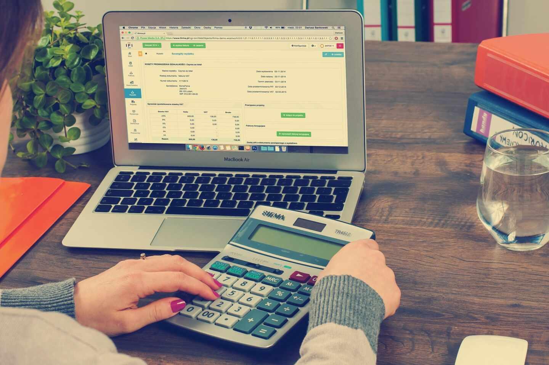 Una mujer comprueba unas cifras delante de un ordenador portátil con una calculadora.