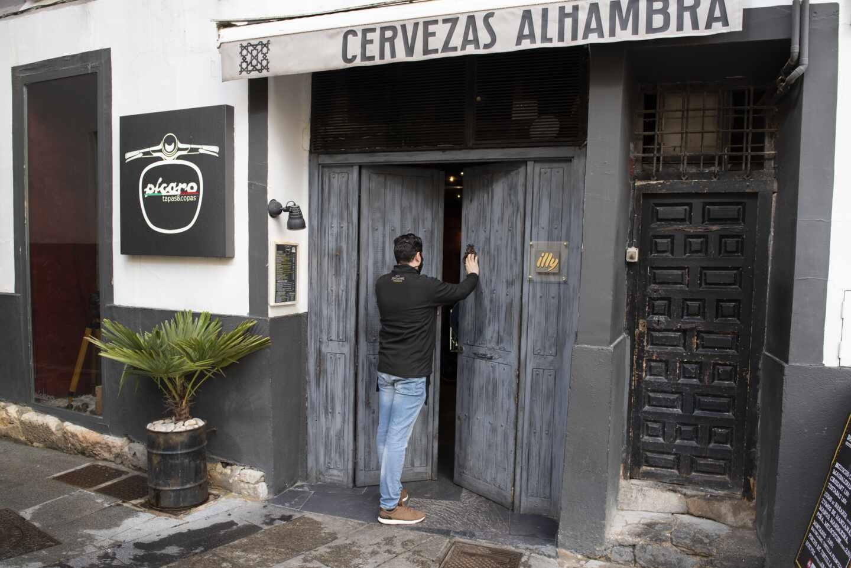 Un hombre abre la puerta de un bar cerrado.