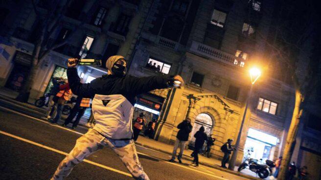 Un manifestante se dispone a lanzar una botella a la policía durante una protesta en Barcelona por Pablo Hasél.