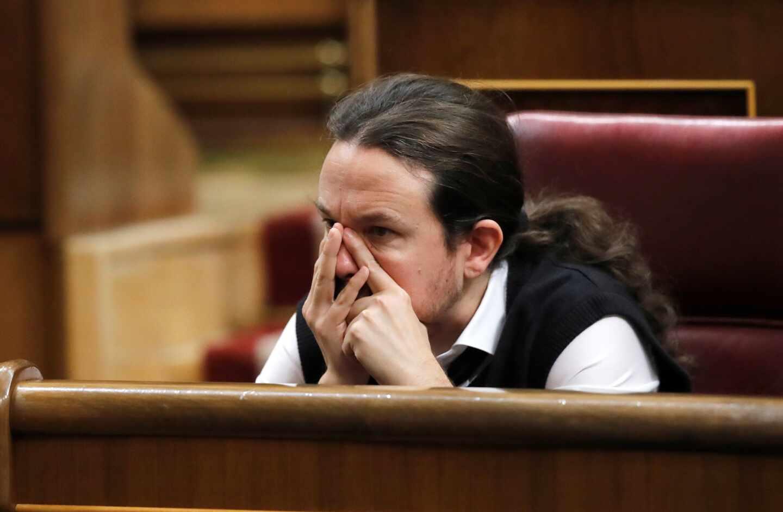 El líder de Podemos, Pablo Iglesias, se toca la cara durante el debate de investidura de Pedro Sánchez.