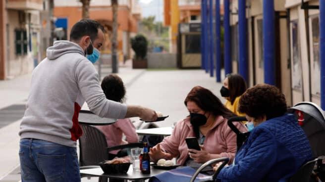 Un camarero atiende a dos clientas en la terraza de un bar.