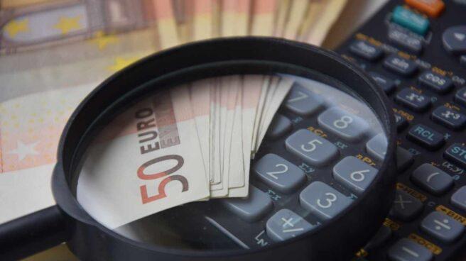 Calculadora junto a billetes y una lupa
