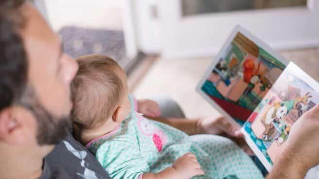 Un padre lee un cuento a su hijo pequeño.