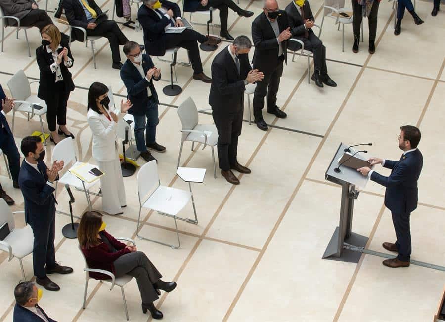 Los diputados de ERC aplauden a Pere Aragonés tras su discurso de investidura, mientras los de JxCat permanecen sentandos