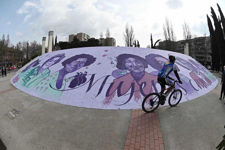 Un ciclista pasa ante el mural feminista al aire libre situado en el paseo de Pastrana de Alcalá de Henares