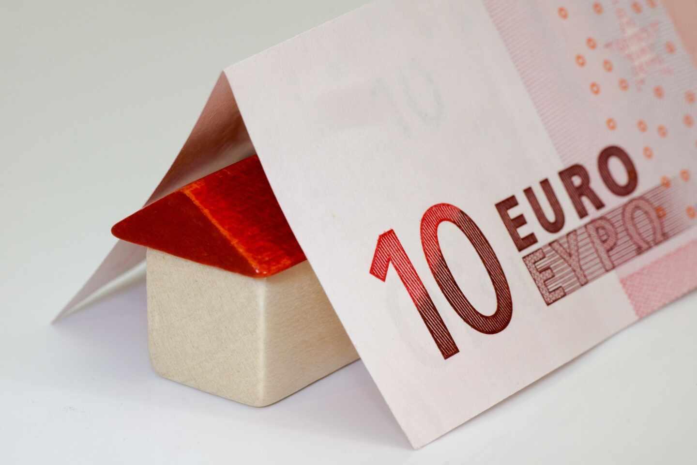 Un billete doblado en forma de tejado sobre una casita de juguete.