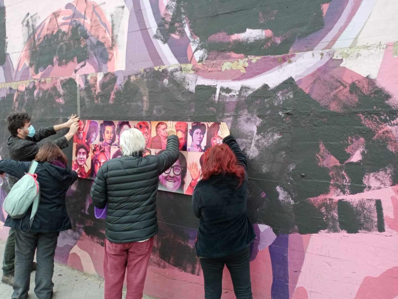 Varios vecinos colocan rostros de mujeres sobre el mural vandalizado de Ciudad Lineal.