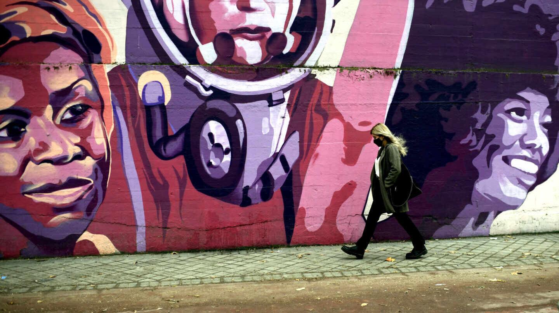 Una mujer pasa por el mural feminista en el polideportivo municipal de la Concepción en el distrito de Ciudad Lineal (Madrid).