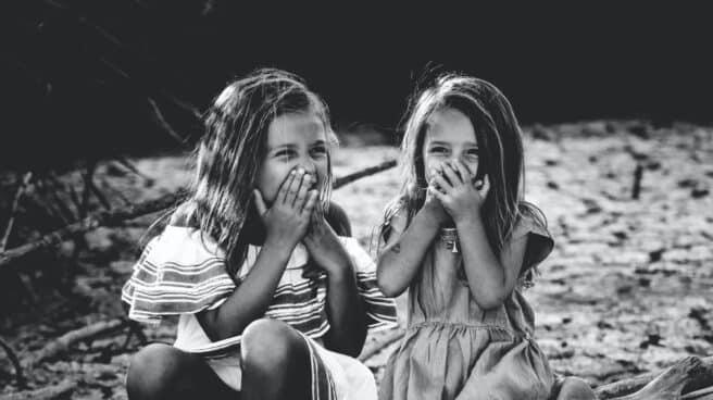Dos niñas sonríen con las manos en la boca.