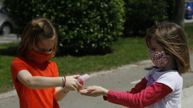 Dos niñas con mascarillas se limpian las manos