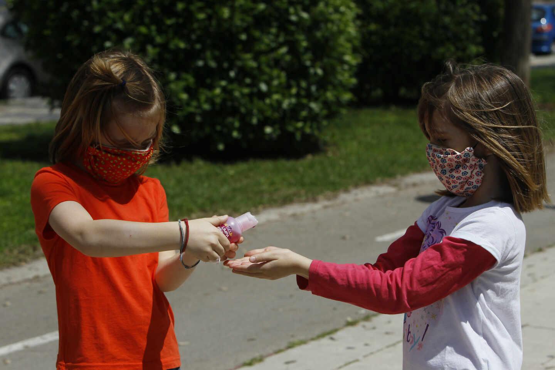 Dos niñas con mascarillas se limpian las manos con solución hidroalcohólica en la calle.