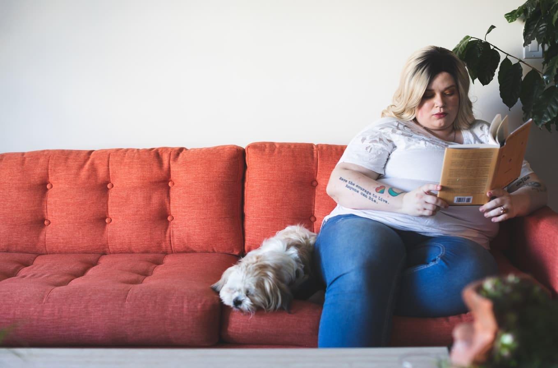 Una persona con obesidad lee un libro sentada en un sofá al lado de un perro.