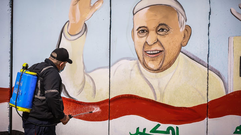 Un obrero fumiga la imagen de un cartel que anuncia la visita del Papa a Irak