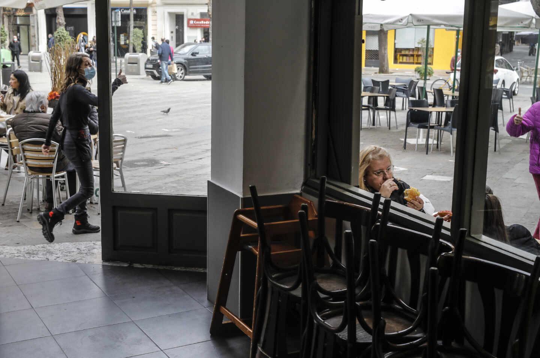 Imagen de un bar con mesas recogidas en el interior y con la terraza abierta.