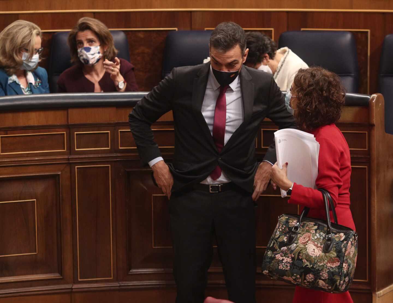 El presidente del Gobierno, Pedro Sánchez, habla con la ministra de Hacienda y portavoz del Gobierno, María Jesús Montero, en el Congreso de los diputados.