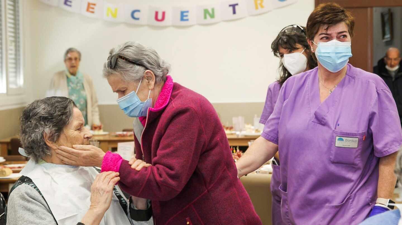 Dos personas mayores reencontrándose en una residencia de ancianos con personal sanitario y mascarillas.