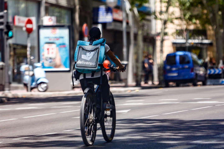 Un 'rider' de la compañía de comida a domicilio, Deliveroo, circula con su bicicleta por una calle de Madrid.