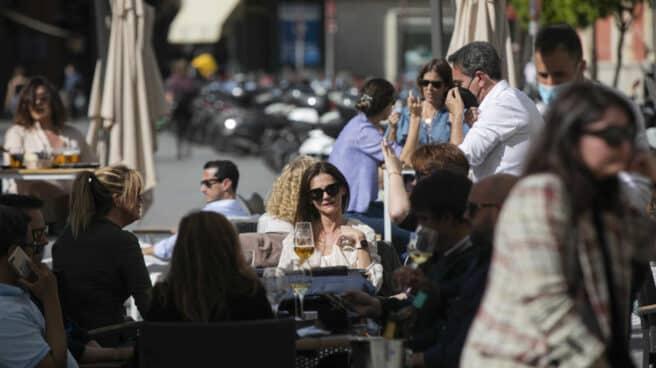 Personas en la terraza de un bar en Sevilla, en Andalucía.