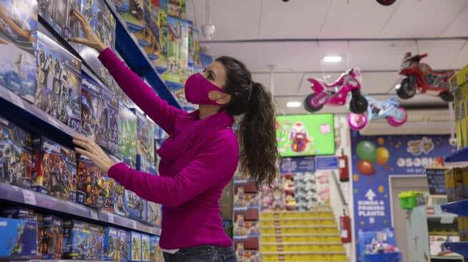 Una trabajadora de la juguetería Osorno, en Sevilla, ordena las estanterías.