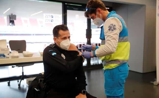 Un policía recibe una dosis de la vacuna de AstraZeneca en el estadio Wanda Metropolitano