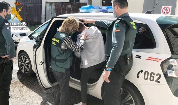 Uno de los detenidos entrando esposado al vehículo de la Guardia Civil