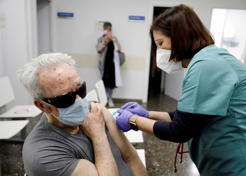 Una sanitaria vacuna a una persona mayor en un ambulatorio de Valencia.