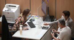 Una trabajadora de una oficina de la Agencia Tributaria en Madrid atiende a dos contribuyentes.