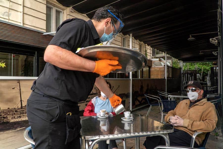 Un camarero sirve en una terraza de Santander.