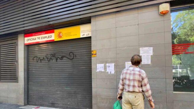 Una persona observa uno de los carteles con instrucciones para hacer trámites por internet colocados en la fachada de una oficina del SEPE.