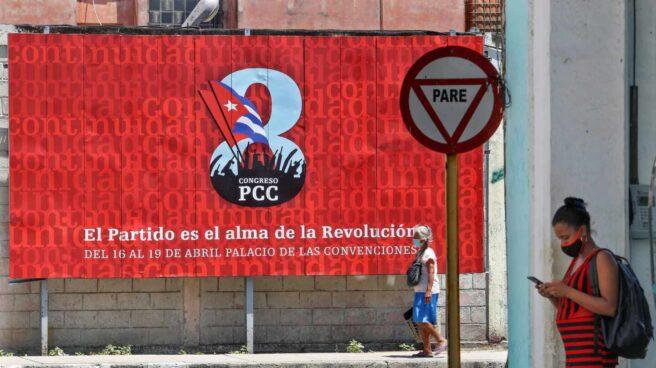 Una cubana consulta el móvil ante un cartel sobre el VIII Congreso del Partido Comunista de Cuba