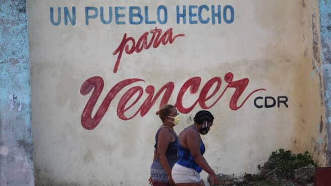Dos cubanas pasan debajo de un lema castrista en La Habana