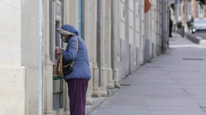 Una mujer protegida con mascarilla y abrigada saca dinero de un cajero.