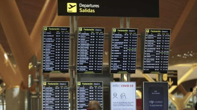 Pasajeros junto a paneles de información en la Terminal T4 del aeropuerto Adolfo Suárez Madrid-Barajas, en Madrid