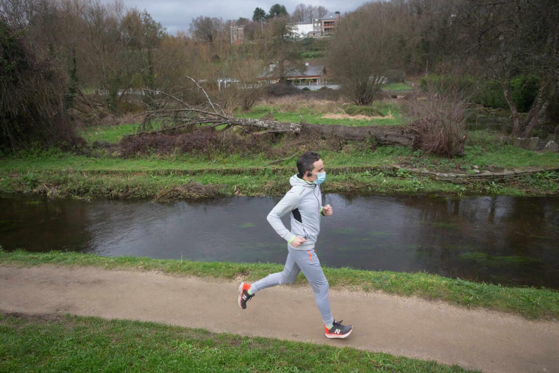 Un hombre corre frente al río Rato, antes del temporal Justine, en Lugo
