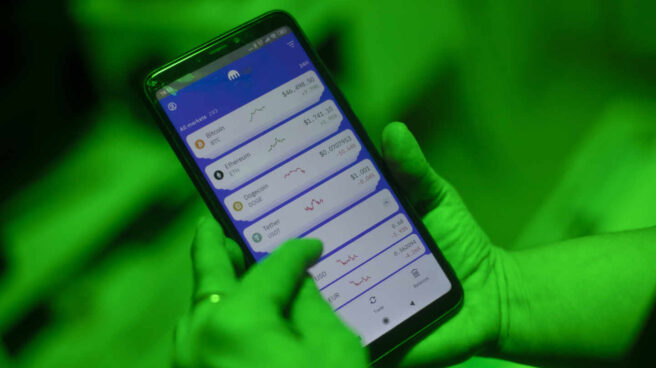 Una internauta utiliza la aplicación Kraken para invertir en criptomonedas, en Madrid