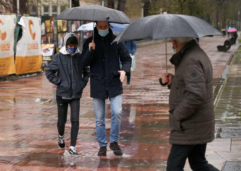Varias personas se refugian con un paraguas de la lluvia en Vitoria, País Vasco