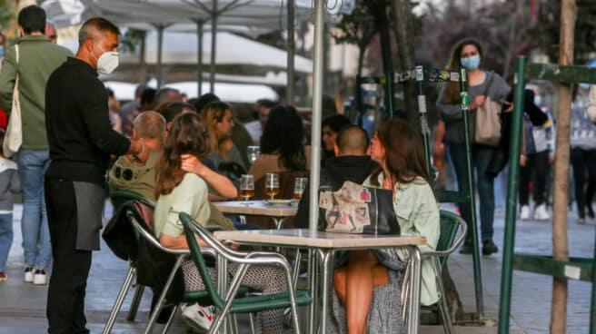 Varias personas conversan en una terraza de Madrid.