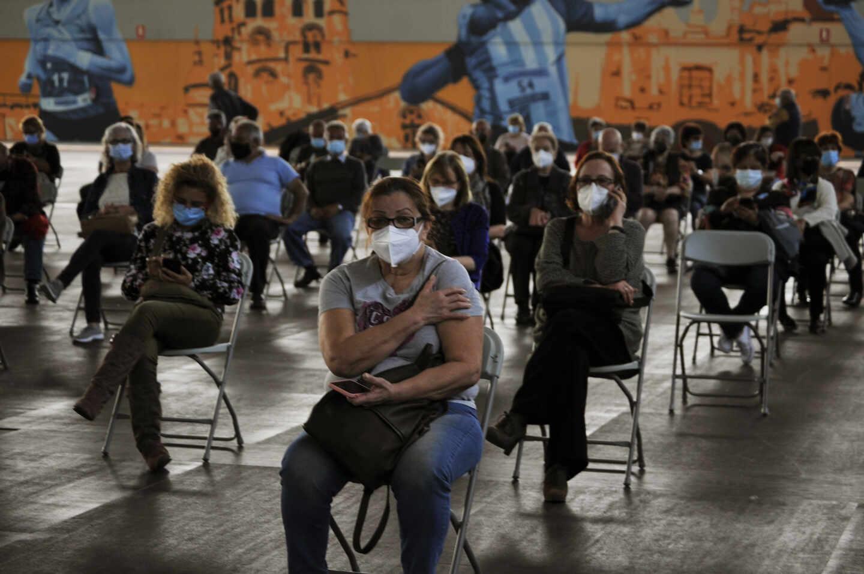 Fila de pacientes que esperan sentados tras recibir la primera dosis de la vacuna AstraZeneca en el recinto de Expourense, a 6 de abril de 2021, en Ourense