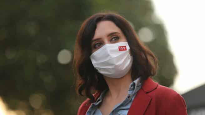 La presidenta de la Comunidad de Madrid y candidata a la reelección, Isabel Díaz Ayuso, porta una mascarilla con la bandera de la región.