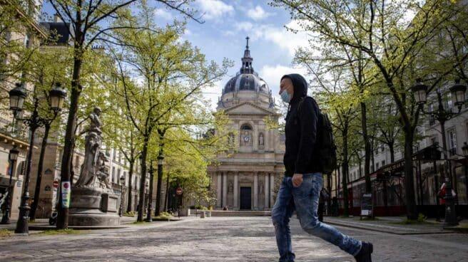 Un hombre camina delante de la Universidad de la Sorbona en París