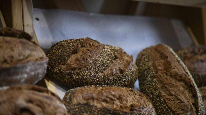 Unas hogazas de pan de semillas en el mostrador de una panadería.
