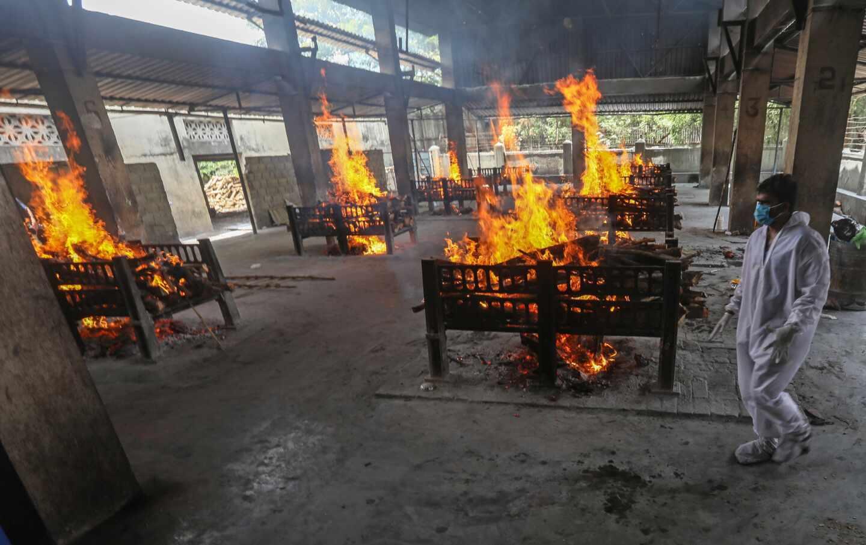 Un operario crema varios cuerpos en la India, donde la pandemia está haciendo estragos