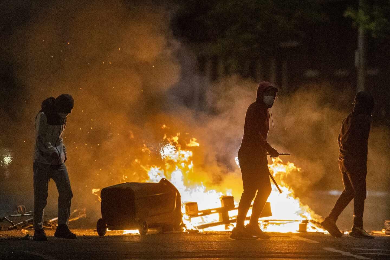 Un grupo de jóvenes contempla cómo arden objetos tras una noche de disturbios en el Ulster