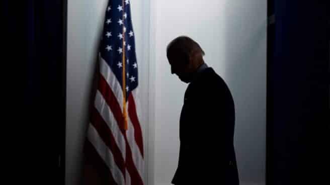 Joe Biden, presidente de EEUU, entre sombras, junto a la bandera de EEUU