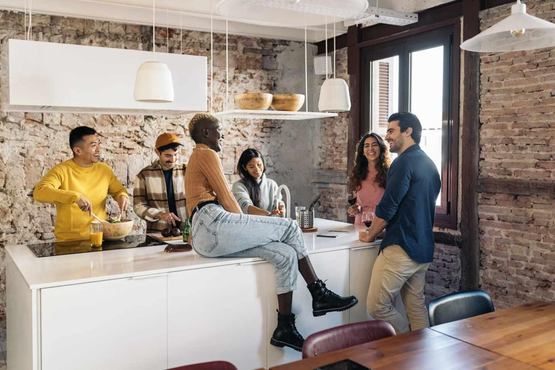 Un grupo de jóvenes charlando en una cocina de un coliving
